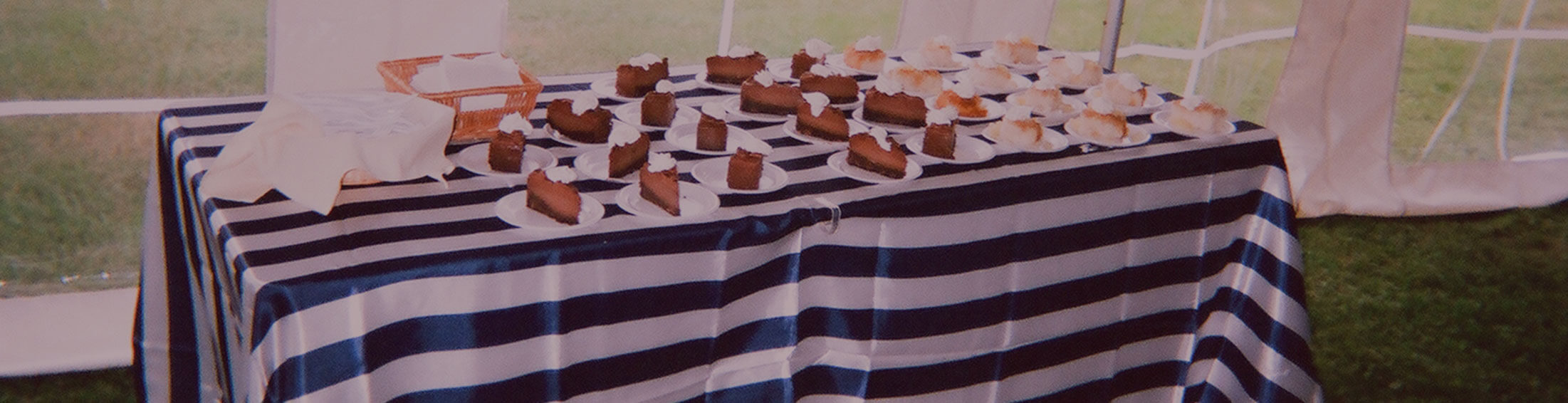 Wedding reception dessert table covered with a navy blue and white stripped tablecloth and filled with plated slices of pie